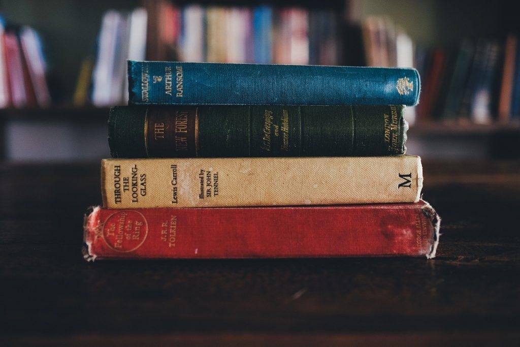 Ein Stapel Bücher, unter anderem J.R.R. Tolkiens Herr der Ringe. Ein Buch, das Generationen überdauert, entsteht in Zusammenarbeit, u.a. zwischen Autor*in und Lektorat.