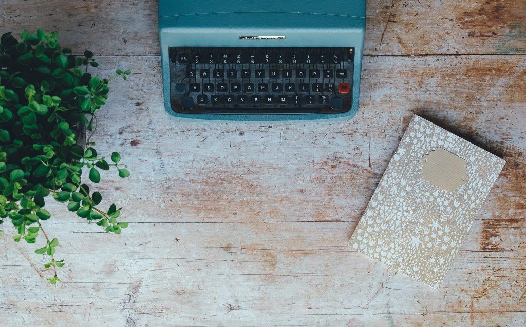 Ein Schreibtisch mit Schreibmaschine und Schreibheft. Hau in die Tasten, schick mir deinen Text und lass uns gemeinsam etwas Großes daraus machen!